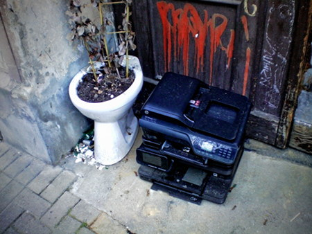 Eine Toilettenschüssel, in der eine (mittlerweile verdorrte) Pflanze gepflanzt wurde, steht in einem Hauseingang neben einem offensichtlich als Müll abgestellten Multifunktionsdrucker von hp.