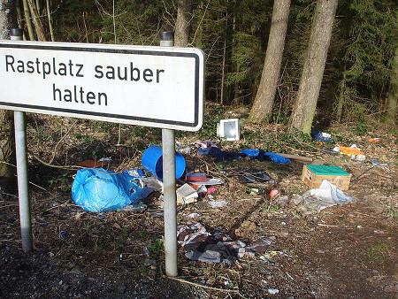 Total vermüllter Autobahnrastplatz in der BRD mit einem Schild 'Rastplatz sauber halten'.