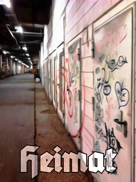 Zwar weichgezeichnete, aber dennoch unendlich triste Szene eines Ganges im Ihmezentrum in Hannover. Darunter das Wort 'Heimat'.