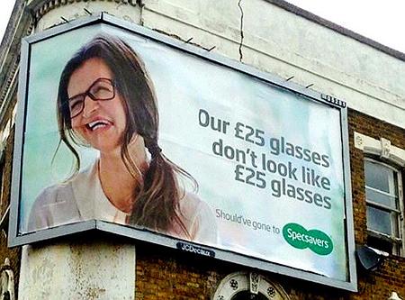 Ein Werbeplakat, das anpreist, wie gut und teuer die preiswerten Brillen aussehen, das aber so geknickt an ein Gebäude plakatiert wurde, dass das Gesicht ausgesprochen unvorteilhaft aussieht.