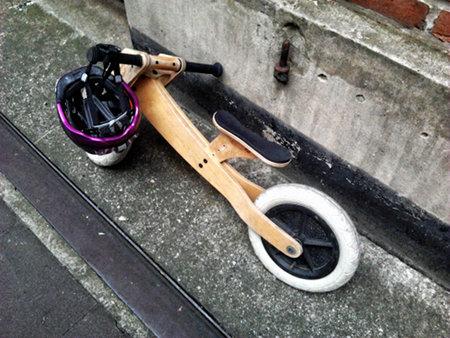 Kleiner, hölzerner Kinderrolle, über dessen Lenkrad ein Fahrradhelm für Kinder hängt