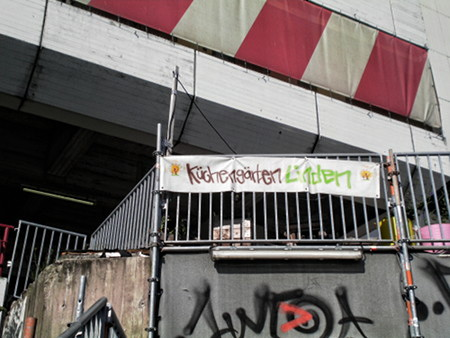 Hilfloser Propaganda- und Dekorationsversuch an der Ruine des Ihmezentrums. An einigen Anpflanzungen ein Transparent in Graffito-Ästhetik: Küchengärten Linden