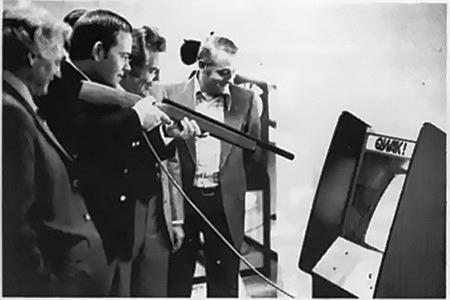 Foto aus einem Fachmagazin für Automatenaufsteller aus dem Jahr 1975. Jemand schießt mit einem Lichtstift-Gewehr auf eine Arcade-Automaten namens Qwak.