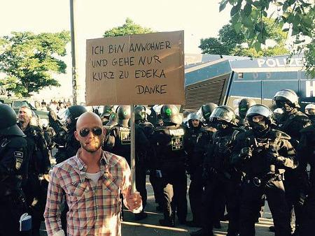 Foto am Rande des laufenden G20 in Hamburg. Mann geht an der voll ausgerüsteten Polizei (mit Wasserwerfer im Hintergrund) vorbei und hält ein Pappschild hoch: 'Ich bin Anwohner und gehe nur kurz zu Edeka. Danke'.