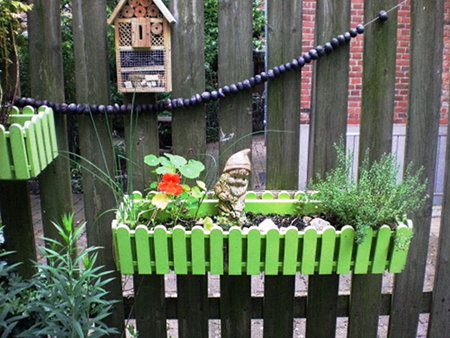 An einem Zaun gehängter Blumenkasten mit Gartenzwerg.