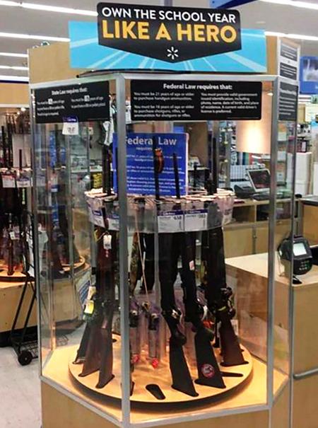 Foto aus den USA. Gewehre in einer Verkaufsvitrine. Darüber eine Werbung 'Own the school year like a hero'.