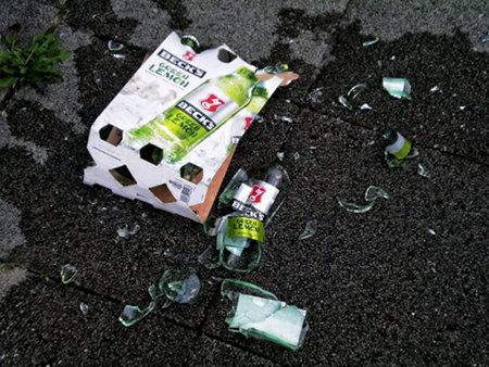 6er-Träger Becks Green Lemon, der zu Boden gefallen ist, nebst kaputter, zersplitterter Flasche in einem großen nassen Fleck