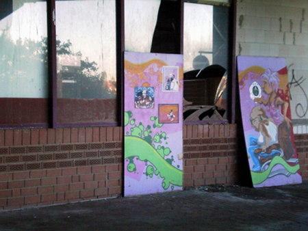 Eingeschlagene Fenster im Ihmezentrum, an denen bunt bemalte Holzabdeckungen gelehnt sind, das alles in einer Umgebung aus Zerfall und Dreck