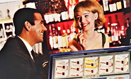 Detail aus einer Reklame aus dem Jahr 1965. Mann und Frau begegnen sich an der Musikbox in einer Kneipe und flirten, natürlich mit unvermeidlichem Schnaps und unvermeidlicher Zigarette.