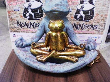 Tinnef: Goldener Frosch, meditierend, auf einem größeren meditierenden Frosch gelagert. Dahinter ein Plakat für eine Veranstaltung namens Non(n)sens.