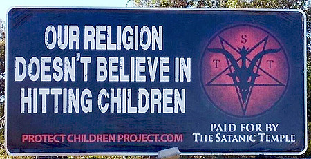 An eine Straße in den USA aufgestelltes Schild: Our religion doesn't believe in hitting children -- protectchildrenproject.com -- Paid for by The Satanic Temple