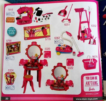 Eine aktuelle Werbung für Barbie-Produkte aus einem Spielzeugkatalog. Alles ist in Pink. Eine Nähmaschine, ein Kehrblech mit Handfeger, Putzzeug, Fön, Kosmetik, Spiegel, Einkaufskorb, Staubsauger, Schmuck. Dazu der Werbetext: You can be anything. Barbie. barbie.com
