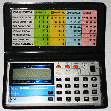 Foto des Taschenrechners Casio FT-7 aus dem Jahr 1981 mit Wahrsagefunktion, in der Hülle eine Karte, die erläutert, wie die Anzeigen für Gesundheit, Glück im Spiel, Geschäft und Liebe zu verstehen sind