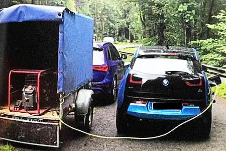 Elektroauto wird am Straßenrand von einem Fahrer eines Kleintransporters aufgeladen -- mit einem Dieselgenerator.