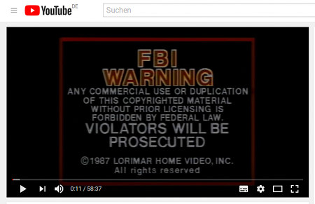 Screenshot YouTube. Sichtbar im abgespielten Video ist die FBI-Warnung an Raubkopierer -- FBI WARNING -- ANY COMMERCIAL USE OR DUPLICATION OF THIS COPYRIGHTED MATERIAL WITHOUT PRIOR LICENSING IS FORBIDDEN BY FEDERAL LAW -- VIOLATORS WILL BE PROSECUTED -- ©1987 LORIMAR HOME VIDEO INC. All rights reserved.
