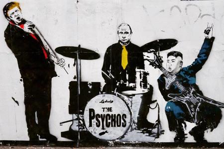 Graffito. Donald Trump hat ein Mikrofon und singt, Wladimir Putin spielt Schlagzeug, Kim Jong Un spielt Gitarre. Bandname: The Psychos.