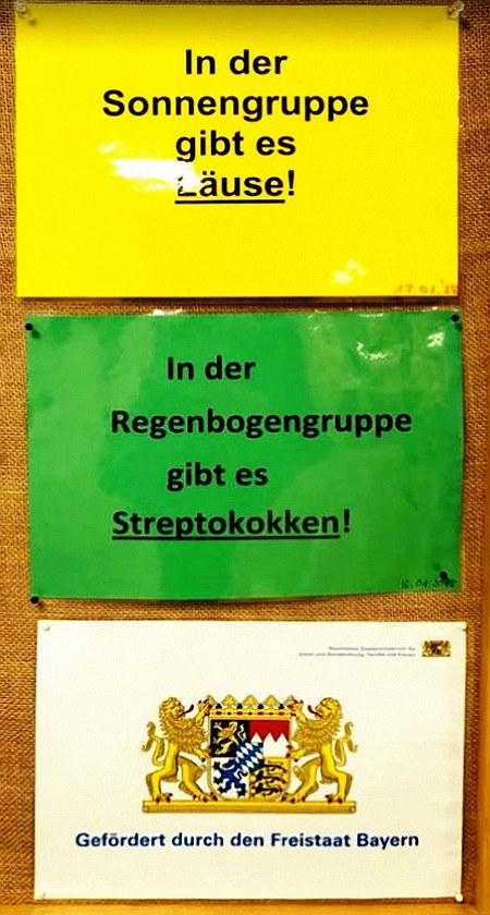 Schwarzes Brett in einem Kindergarten. -- In der Sonnengruppe gibt es Läuse! -- In der Regenbogengruppe gibt es Streptokokken! -- Gefördert durch den Freistaat Bayern
