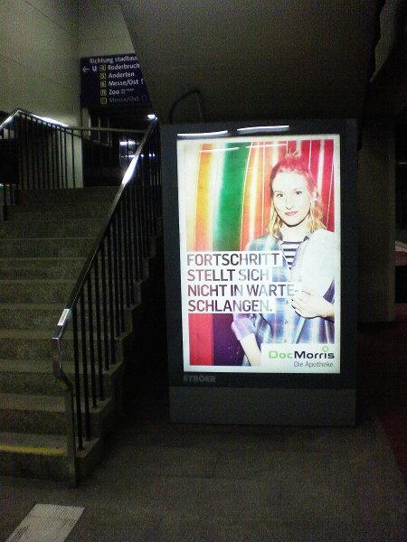 Leuchtende Werbung für die Online-Apotheke Doc Morris 'FORTSCHRITT STELLT SICH NICHT IN WARTESCHLANGEN' in der grauen Tristesse der U-Bahn-Station Aegidientorplatz.
