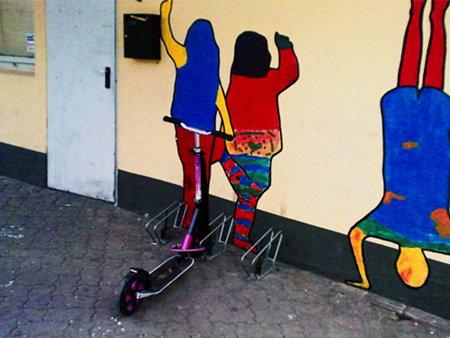 Ein Kinderroller, der an einem Fahrradständer an einer (sehr bunt bemalten) Wand abgestellt wurde.