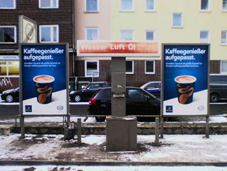 Stillleben an einer Tankstelle. Wasser, Luft und Öl umgeben von zwei Werbeplakaten für den überteuerten Kaffee an der Tankstelle.
