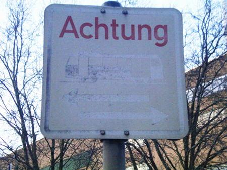 Verblichenes Verkehrsschild, das davor warnen soll, dass in beiden Richtungen Straßenbahnen fahren. Nur noch das rote Wort 'Achtung' ist erkennbar.
