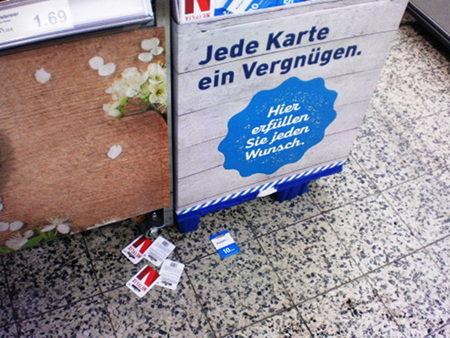 Foto aus einem Aldi-Nord-Markt. Werbung unter den diversen Telefon, iTunes und Netflix-Karten: Jede Karte ein Vergnügen. Hier erfüllen Sie jeden Wunsch. Achtlos auf dem Boden liegen heruntergefallene oder heruntergeworfene Karten, mit denen man einen Kassenbon kaufen kann.