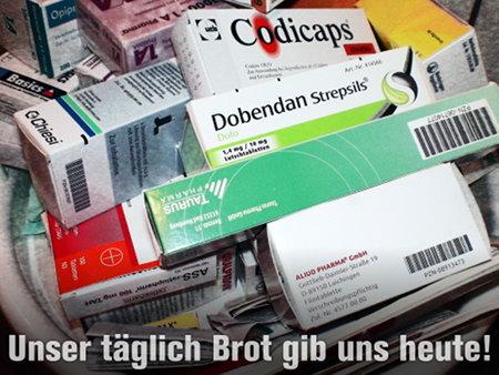 Ein beachtlicher Haufen von Medikamentenpackungen, darunter der Text: Unser täglich Brot gib uns heute!