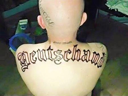 Tätowierter Rücken mit dem in Fraktur geschriebenen Wort 'Deutschand'.