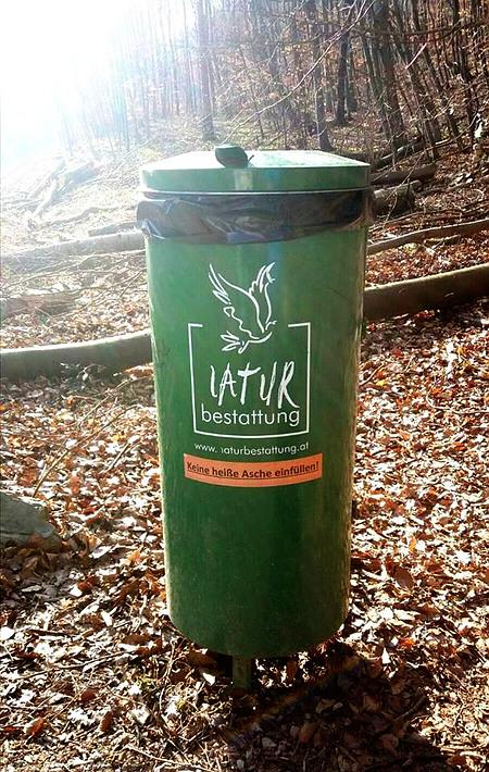 Mülltonne an einem Waldweg mit Werbung: Naturbestattung -- www.naturbestattung.at -- Darunter der typische Aufkleber 'Keine heiße Asche einfüllen!'.