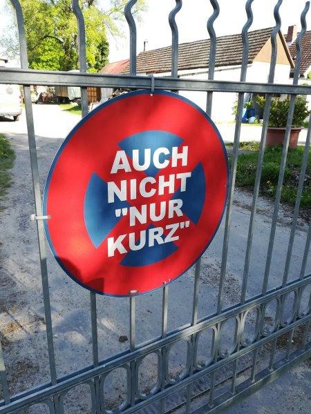 Verkehrszeichen Absolutes Halteverbot an einer Einfahrt, auf dem der Text 'AUCH NICHT NUR KURZ' geschrieben ist.