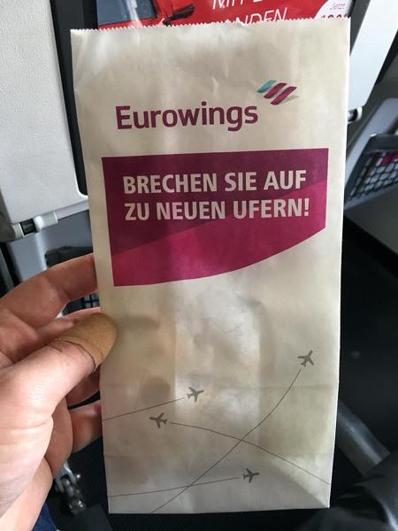 Speitüte in einem Flugzeug, mit Eurowings-Reklame-Aufdruck: Brechen Sie auf zu neuen Ufern!