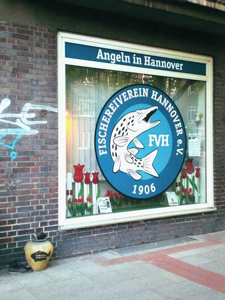 Stillleben auf der Hildesheimer Straße in Hannover. Vor dem Fischereiverein steht im Müll eine Vase mit Fischmotiv, dazu ein altes Paar Schuhe.