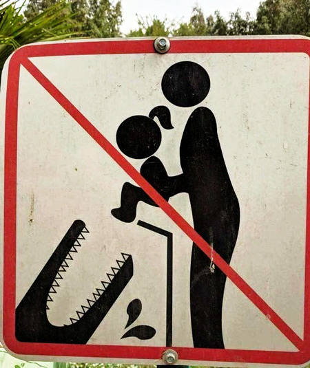 Absurdes Schild... Piktogramm eines Erwachsenen, der das Piktogramm eines Babies in das Piktogramm eines aufgerissenen Krokodilsrachens wirft, durchgestrichen, weil es verboten ist...