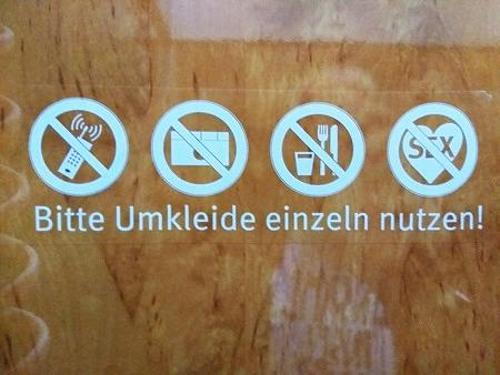 Vier Pinktogramme: Keine Handys, keine Fotos, kein Essen und Trinken, kein Sex. Darunter der Text: Bitte Umkleide einzeln nutzen!