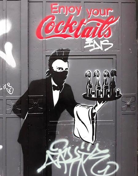 Graffito. Ein maskierter Kellner mit Irokesenfrisur serviert auf einem Tablett vier Molotow-Cocktails in Coca-Cola-Flaschen und ein Feuerzeug. Darüber in den typischen Coca-Cola-Schriftarten: Enjoy your Cocktails