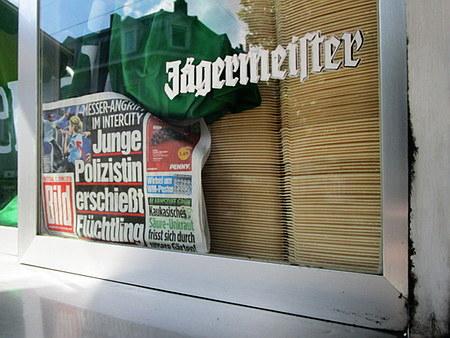 Fenster, beklebt mit einer Jägermeister-Werbung. In diesem Fenster eine Bildzeitung mit der Schlagzeile 'Messer-Angriff im Intercity: Junge Polizistin erschießt Flüchtling'.