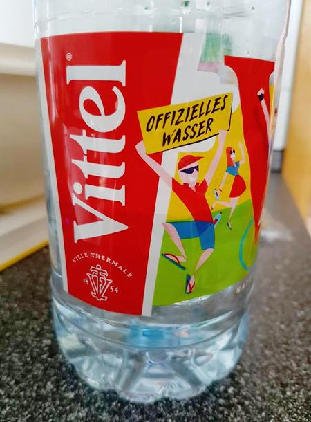 Flasche Vittel-Mineralwasser mit Etikettenaufdruck 'Offizielles Wasser'.