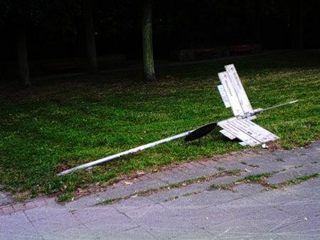 Vandalismus an einem Wegweiser, der umgekippt auf dem Boden im Gras liegt.