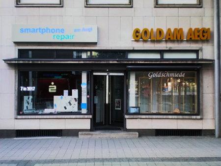Zwei Läden am Aegidientorplatz, Hannover, die sich einen Eingang teilen. Links 'smartphone repair am Aegi', rechts 'GOLD AM AEGI'.