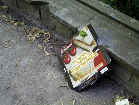 Auf den Weg weggeworfene Pizzaverpackung mit Werbeaufdruck: Domino's -- Wir machen unseren Teig jeden Tag frisch