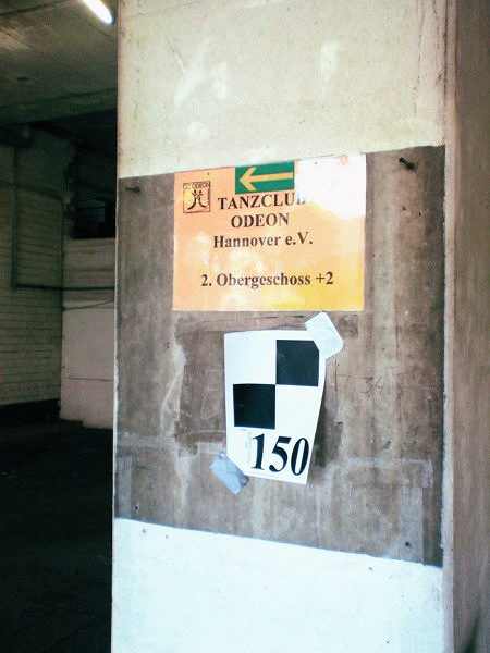 Hinweis an einem Betonpfeiler im Ihmezentrum: TANZCLUB ODEON Hannover e.V., 2. Obergeschoss +2, darunter eine Vermessungsmarke. Drumherum Beton, Dreck und Zerfall.