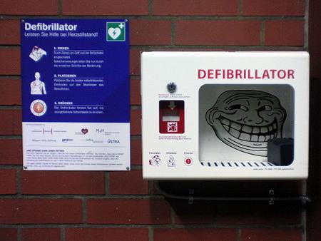 Leerer Defibrillator neben einer Anleitung, wie man Erste Hilfe bei Herzstillstand leistet. In den Behälter für den Defibrillator ist das Trollface montiert
