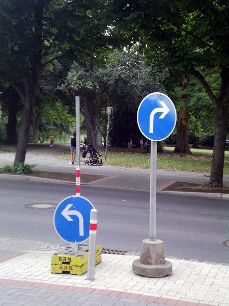 Zwei Verkehrszeichen nebeneinader. Einmal vorgeschriebene Fahrtrichtung links, einmal vorgeschriebene Fahrtrichtung rechts.