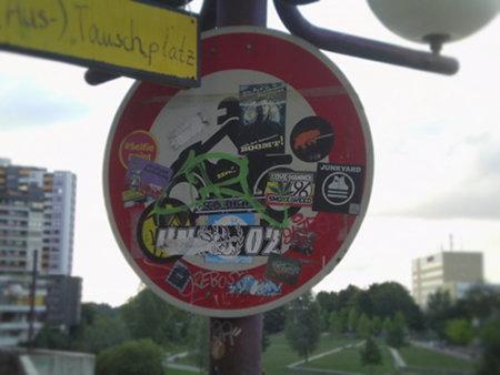 Stark mit Aufklebern beklebtes Verkehrsschild in der Ruine des Ihmezentrums in Hannover-Linden