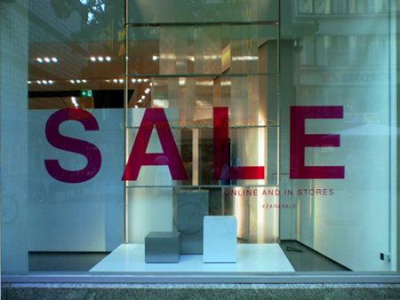 Leeres, völlig undekoriertes Schaufenster, in dem mit großen Buchstaben 'SALE' steht.