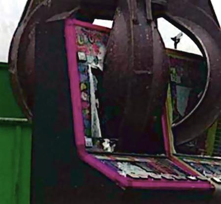 Ein alter Arcade-Unterhaltungsautomat wird äußerst unsanft mit einer Greifzange in einen Müllcointainer befördert