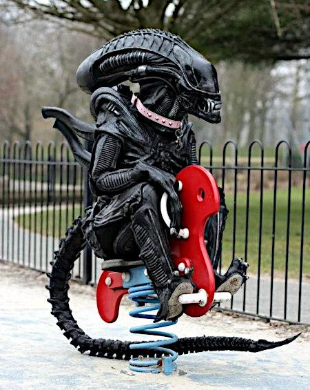 Alien auf einem Schaukelpferd auf einem Spielplatz