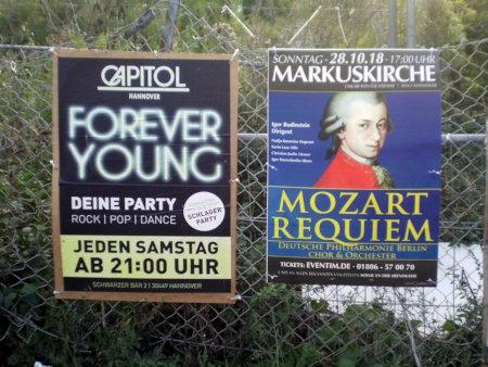 Zwei Plakate nebeneinader -- 'CAPITOL HANNOVER -- FOREVER YOUNG -- DEINE PARTY' und 'MARKUSKIRCHE MOZART REQUIEM'.