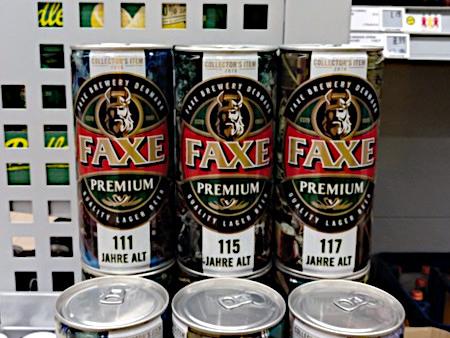 Drei Dosen Bier, Marke Faxe, die nebeneinanderstehen. Auf der ersten steht 111 Jahre alt, auf der zweiten 115 Jahre alt, auf der dritten 117 Jahre alt