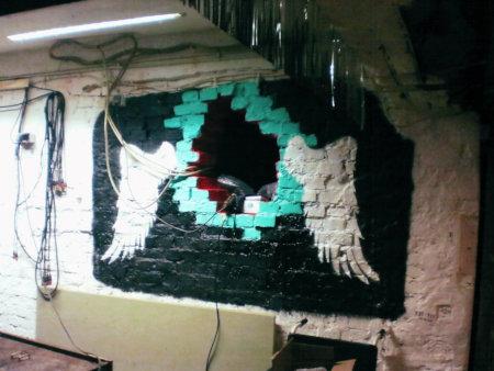 Ein Wanddurchbruch, durch den ein paar Kabel geführt wurden und der sehr dadaistisch wertvoll dekoriert wurde, indem die Wand mit Flügeln bemalt wurde